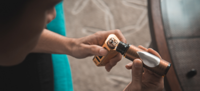 A person filling their e-cigarette with fluid.