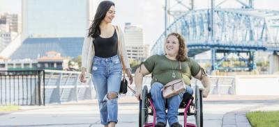 Two women enjoying a bright day on a boardwalk.