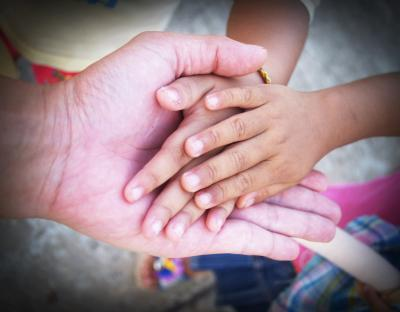 Adult hands holding child's hands