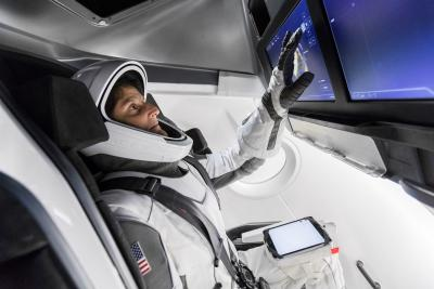 NASA Astronaut Suni Williams, fully suited in SpaceX's spacesuit, interfaces with the display inside a mock-up of the Crew Dragon spacecraft in Hawthorne, California, during a testing exercise on Tuesday, April 3, 2018.
