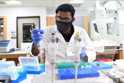 A researcher wearing a face mask works in a lab.