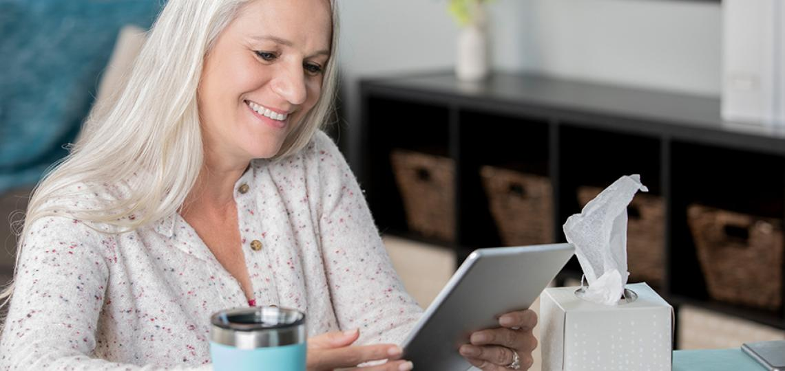 A person at home reading information on a tablet computer