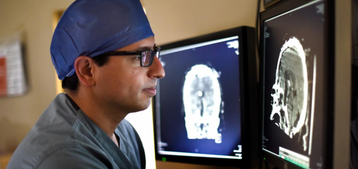 Doctor looking at monitor of brain scans.