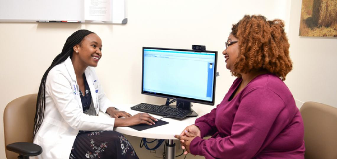 A doctor and her patient are sitting and discussing care and treatment in front of a computer.