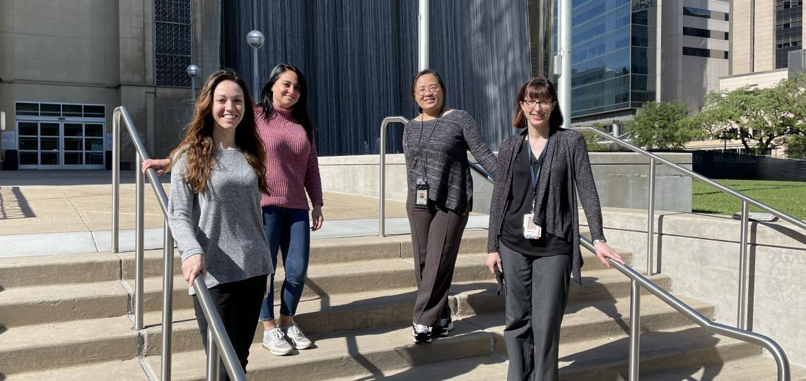 Four women standing on a set of stairs on a sunny day.