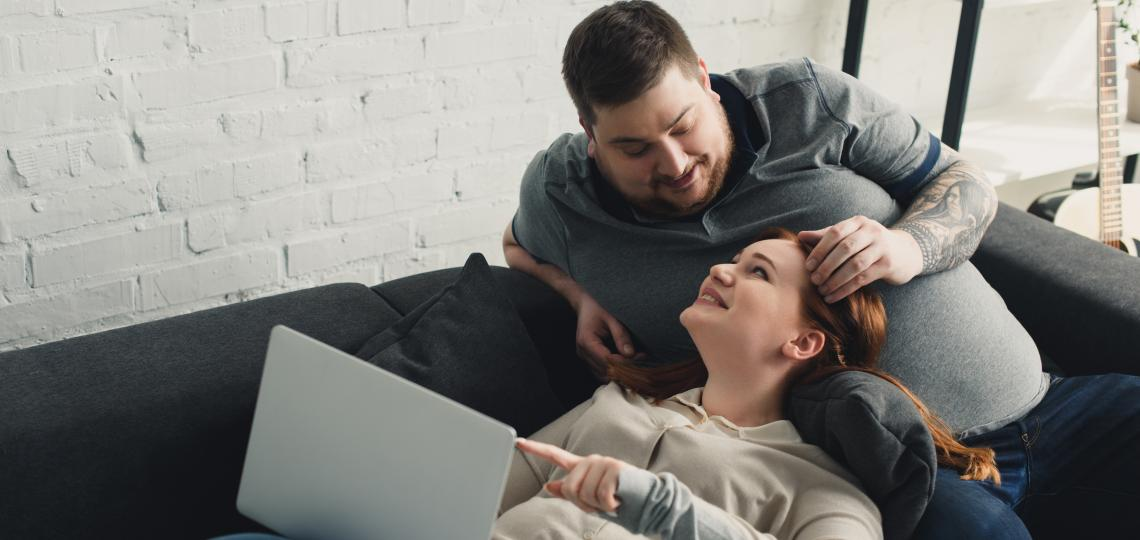 Overweight couple sitting a couch and looking at a laptop computer.