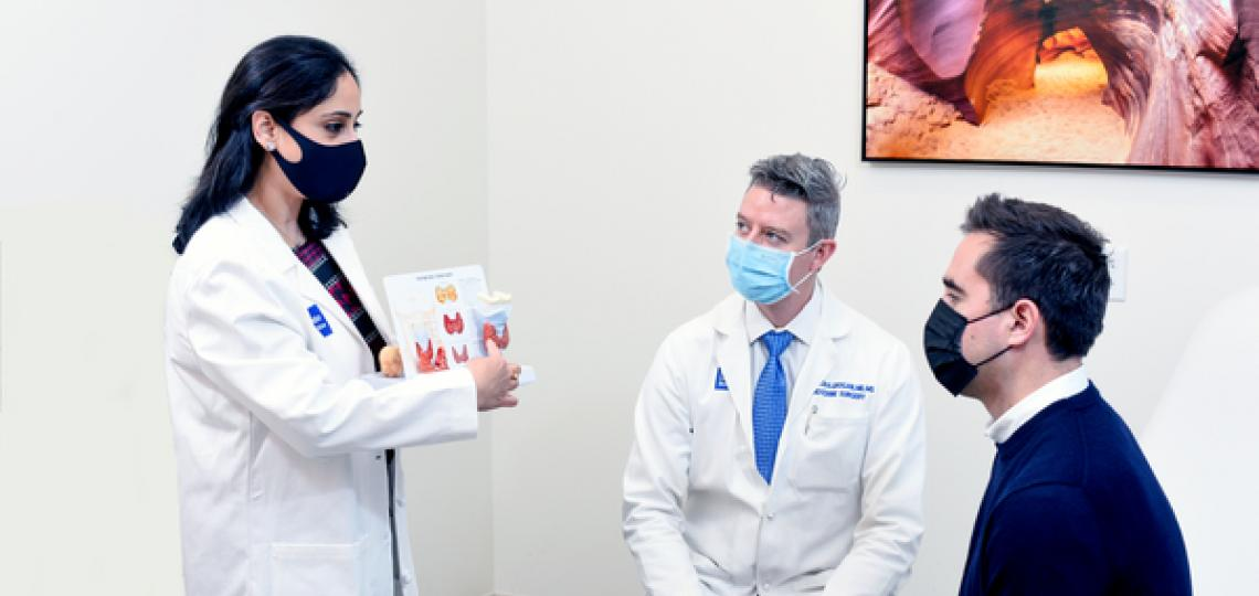 A masked female doctor explaining a diagram of the thyroid and parathyroid to a masked male doctor and masked male patient.