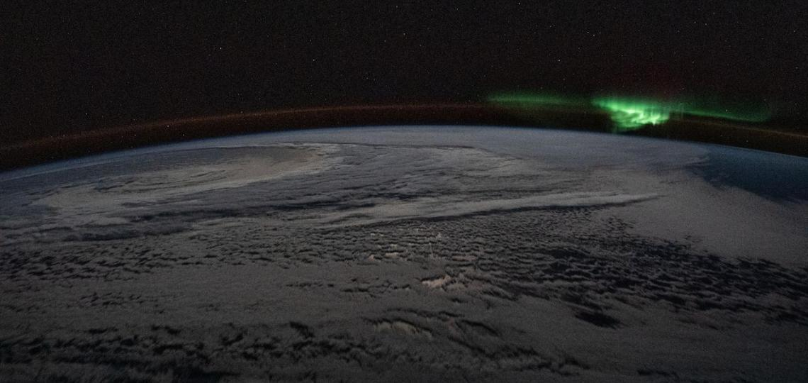 """The atmospheric glow and a wispy aurora australis, also known as the """"southern lights,"""" frame a cloud-covered Earth as the International Space Station orbited 254 miles above the Indian Ocea."""