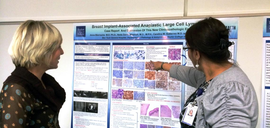 Pathology resident receiving feedback from faculty about her poster presentation.