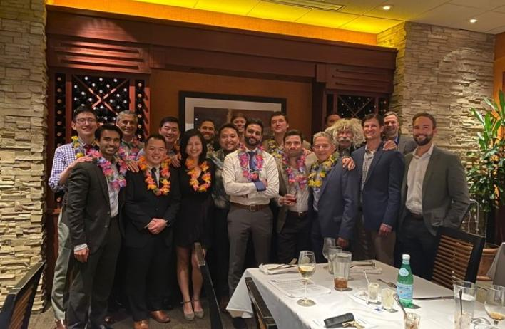Recent R4 graduates at their residency graduation, wearing leis gifted by their coresident Brian Imada.