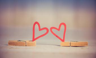 A pair of cartoon hearts held up by clothes pins.