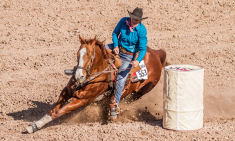 A person riding on a horse in a race, taking a hard turn around a barrel.