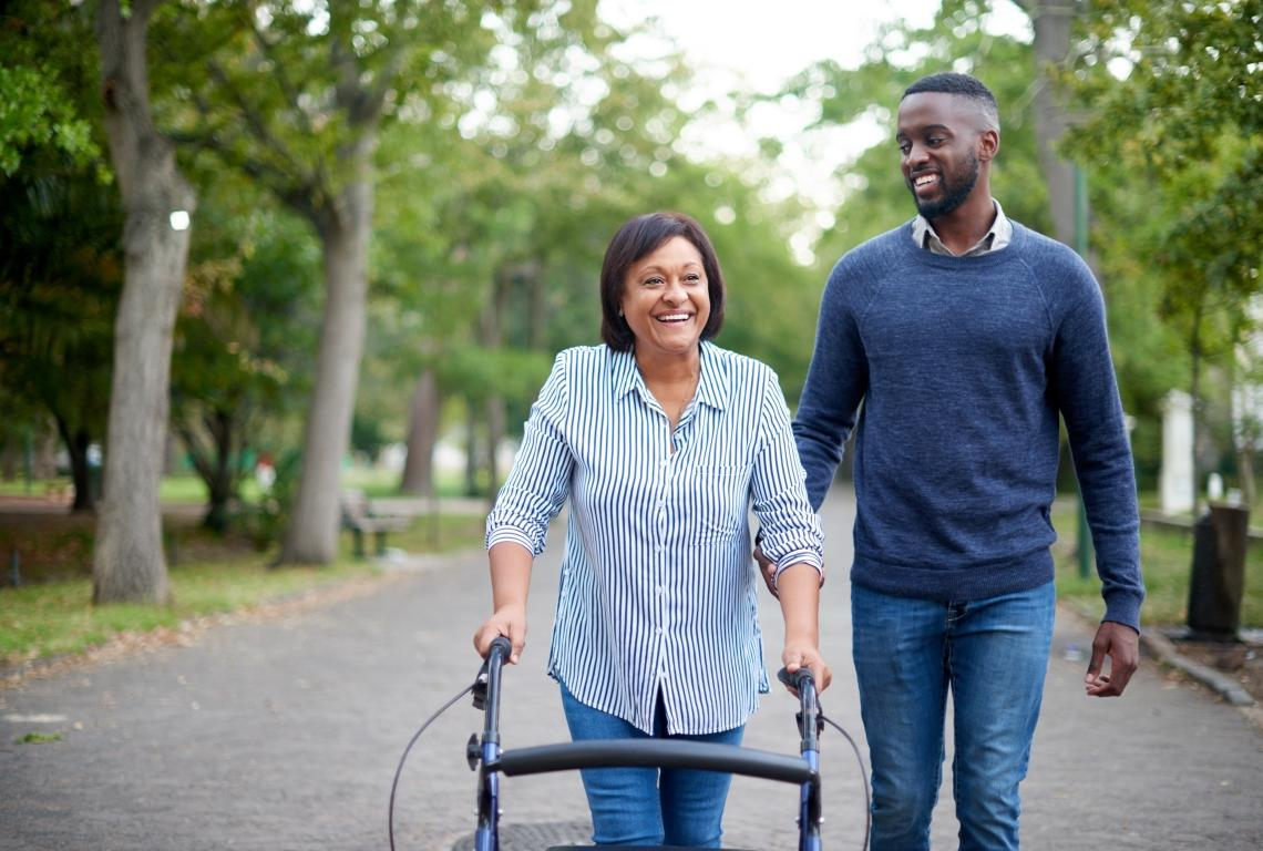 A woman walking with a walker assisted by a loved one.