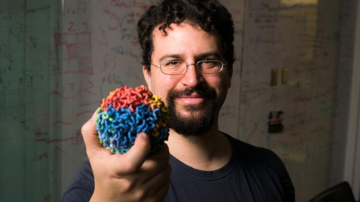 Dr. Erez Lieberman Aiden holds a diagram of a 3D genome map within a cell.