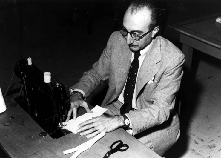 Dr. Michael E. DeBakey sits at his wife's sewing machine fashioning the first artificial arteries for cardiac bypass surgery made of Dacron.