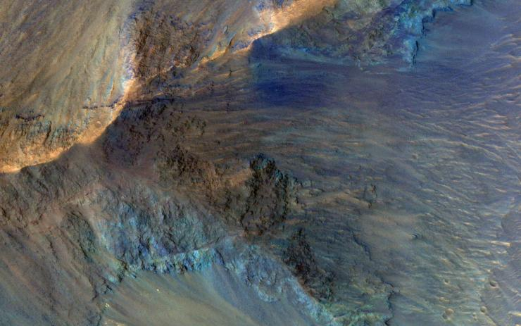 This image captures some of the geologic diversity of Mars. There are hills of ancient terrains on the floor of Juventae Chasma, surrounded by younger sediments, including dark sand sheets and dunes that are likely active today.