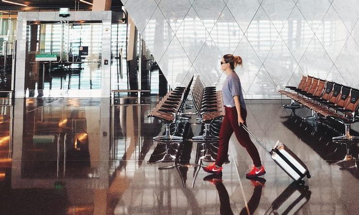 A person walks through an airport on the way to a holiday destination