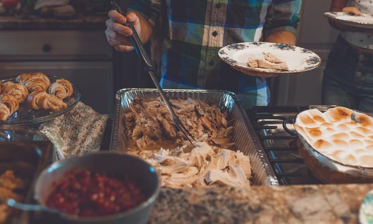 Individuals plating food during a holiday gathering.