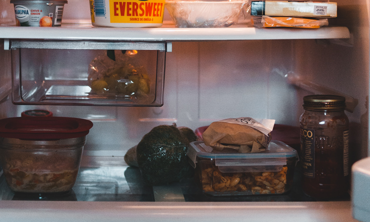 A refrigerator filled with leftover meals, vegetables and dairy products