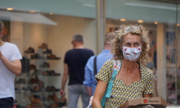 A person wearing a face mask in a mall.