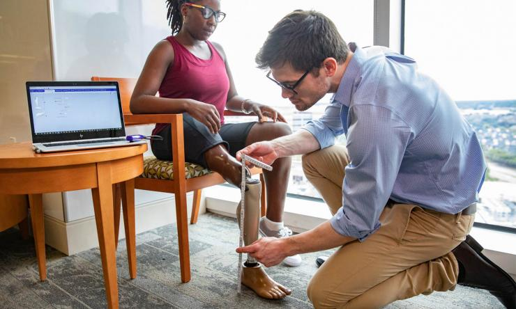 Doctor fitting patient with prosthetic leg