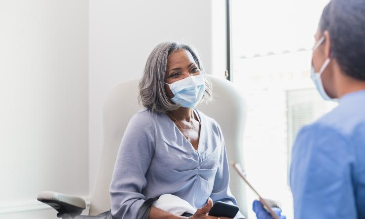 Older female patient wearing a mask over her face and phone in her hand speaking with healthcare professional