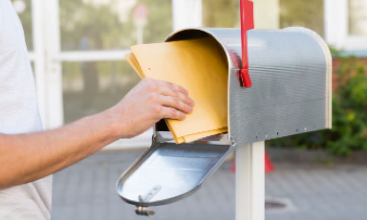 A person putting envelopes into an open mailbox.