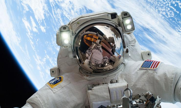 Fellow spacewalker Rick Mastracchio appears in the reflection of Astronaut's Mike Hopkins' helmet.