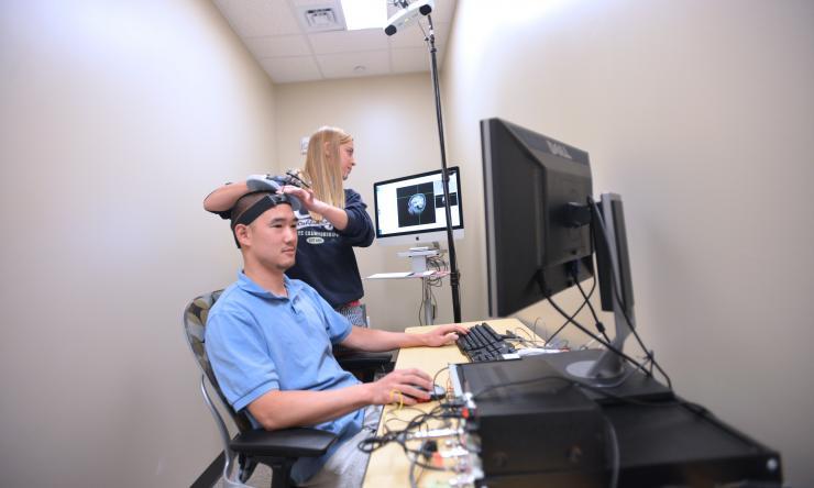 Woman scans patient (wide shot)