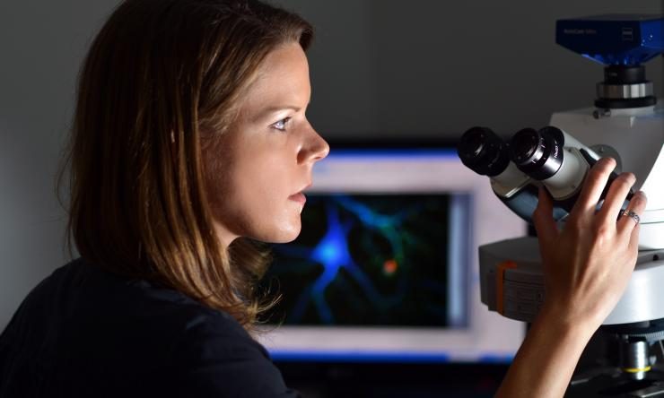 Woman at microscope in the light