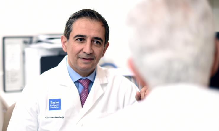 Dr. Hashim El-Serag speaking with colleague