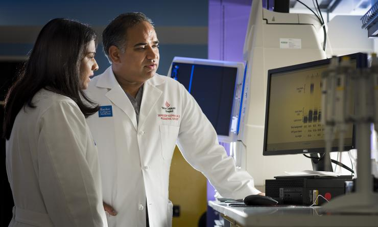 Dr. Sundeep Keswani and colleague reviewing patient files.