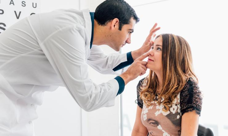 A patient sits while a doctor performs an eye exam.