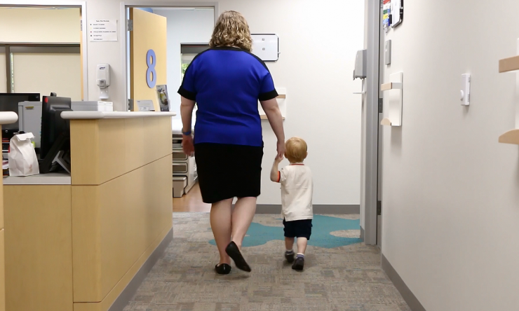 A doctor leads a child into an office to be screened with a Modified Checklist for Autism in Toddler, or M-CHAT.