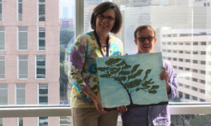 Dr. Cynthia Peacock is presented a painting by patient Brandon Lack for the Transition Medicine Clinic.