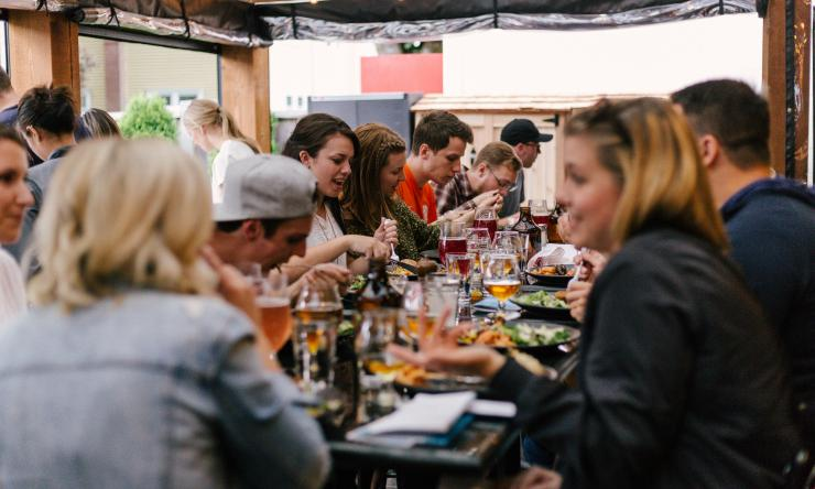 A group of friends enjoy a meal out together in a crowded restaurant.